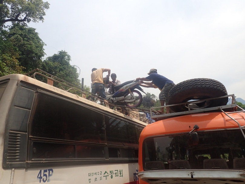 Transferring a scooter from the roof of one bus to another in Laos